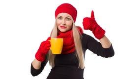 Donna in cappello con la tazza ed il pollice su fotografia stock