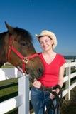 Donna in cappello del cowboy con il cavallo - verticale Immagine Stock