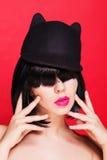Donna in cappello del gatto Cappuccio con le orecchie animali Su rosso Fotografia Stock Libera da Diritti