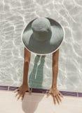 Donna in cappello del sole nella piscina Vista superiore immagine stock