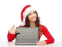 Donna in cappello dell'assistente di Santa con il computer portatile Immagini Stock