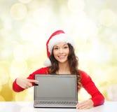 Donna in cappello dell'assistente di Santa con il computer portatile Immagine Stock