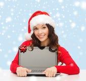 Donna in cappello dell'assistente di Santa con il computer portatile Immagine Stock Libera da Diritti
