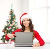 Donna in cappello dell'assistente di Santa con il computer portatile Fotografia Stock