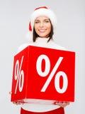 Donna in cappello dell'assistente di Santa con il segno di percentuali Immagine Stock