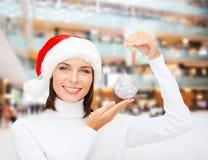 Donna in cappello dell'assistente di Santa con la palla di natale immagine stock libera da diritti