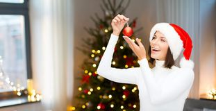 Donna in cappello dell'assistente di Santa con la palla di natale fotografie stock