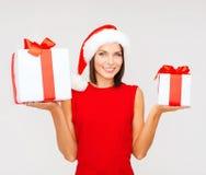 Donna in cappello dell'assistente di Santa con molti contenitori di regalo Fotografia Stock