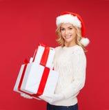 Donna in cappello dell'assistente di Santa con molti contenitori di regalo Fotografie Stock Libere da Diritti