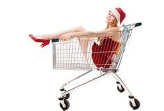 Donna in cappello della Santa che si siede in carrello di acquisto fotografia stock libera da diritti