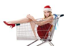 Donna in cappello della Santa che si siede in carrello di acquisto fotografie stock
