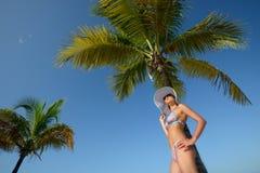 Donna in cappello di estate che prende il sole sotto una palma su un fondo Immagine Stock