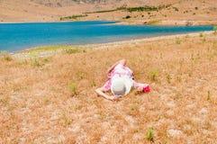 Donna in cappello di paglia che si trova sull'erba asciutta Immagini Stock Libere da Diritti
