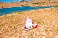 Donna in cappello di paglia che si trova sull'erba asciutta Immagine Stock