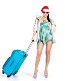 Donna in cappello di Santa che sta con la valigia di viaggio Fotografie Stock