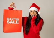Donna in cappello di Santa che tiene il sacchetto della spesa di natale con le vendite scritte su che sembra eccitato e felice fotografie stock libere da diritti