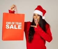 Donna in cappello di Santa che tiene il sacchetto della spesa di natale con le vendite scritte su che sembra eccitato e felice fotografia stock libera da diritti