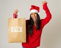 Donna in cappello di Santa che tiene il sacchetto della spesa di natale con le vendite scritte su che sembra eccitato e felice fotografia stock