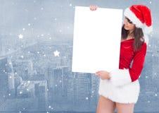 Donna in cappello di Santa che tiene un cartello in bianco Immagini Stock