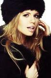 Donna in cappello e cappotto di pelliccia neri Fotografia Stock