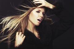 Donna in cappello e cappotto di pelliccia neri immagini stock