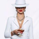 Donna in cappello e cognac della bevanda del vestito Fotografia Stock Libera da Diritti
