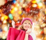 Donna in cappello e sciarpa rosa con i sacchetti della spesa Fotografie Stock
