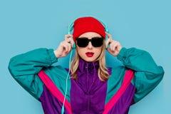Donna in cappello, in occhiali da sole ed in vestito rossi di 90s con le cuffie immagine stock libera da diritti