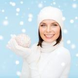 Donna in cappello, in sciarpa ed in guanti con la palla di natale Immagini Stock