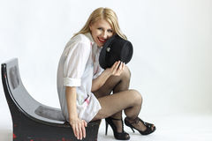 Donna in cappello sulla sedia isolata su fondo bianco Fotografia Stock