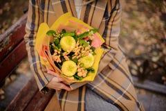 Donna in cappotto del plaid che si siede sul banco con un mazzo dei fiori gialli fotografia stock