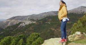 Donna in cappotto giallo vicino alla valle della montagna stock footage
