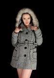 Donna in cappotto grigio su priorità bassa nera Fotografia Stock