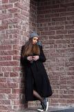 donna in cappotto nero con un caffè da andare immagini stock