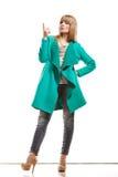 Donna in cappotto verde che mostra lo spazio della copia immagini stock