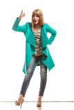 Donna in cappotto verde che mostra lo spazio della copia fotografia stock