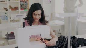 Donna carismatica piacevole che cuce vestito nero facendo uso della macchina per cucire di fabbricazione Sarto femminile professi video d archivio