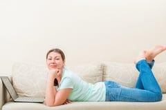 Donna a casa che lavora in Internet fotografia stock