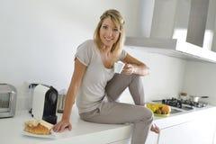 Donna a casa che mangia caffè Fotografia Stock