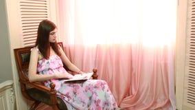 Donna a casa che si siede sulla sedia davanti al libro di lettura della finestra video d archivio