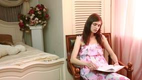 Donna a casa che si siede sulla sedia davanti al libro di lettura della finestra archivi video