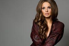 Donna castana abbastanza attraente in rivestimento marrone rossiccio, backgrou grigio immagine stock libera da diritti
