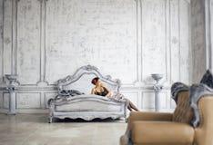 Donna castana abbastanza esile che riposa nella stanza di lusso Fotografie Stock Libere da Diritti