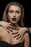 Donna castana abbastanza gotica con le mani sul collo Immagine Stock