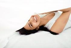 Donna castana abbastanza sveglia a letto sotto gli strati Fotografie Stock Libere da Diritti