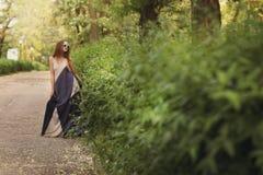 Donna castana adorabile in vestito lungo ed occhiali da sole rotondi Fotografie Stock Libere da Diritti