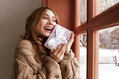 Donna castana affascinante 20s in maglione tricottato che guarda fuori Th Fotografia Stock Libera da Diritti