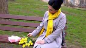 Donna castana allegra che gode dell'odore dei tulipani gialli dati dall'uomo caro stock footage