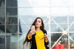 Donna castana allegra in maglione giallo che fa sefie contro il fondo dell'aeroporto Tecnologia moderna fotografia stock