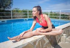 Donna castana attraente che fa allungando esercizio vicino allo swimmin fotografia stock